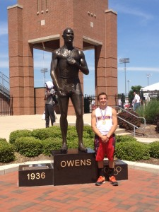Brad Kanney proudly standing next to the Jesse Owens statue at the state track meet, after his 4x100 relay team won the state title.